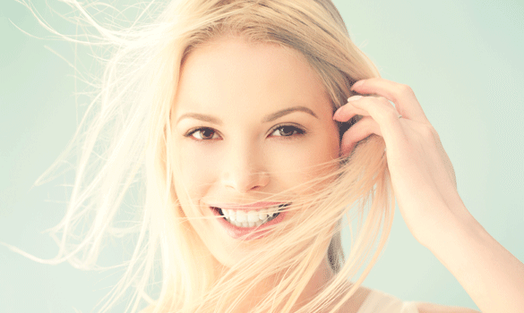 Smiling woman pulling her blonde hair out of her face