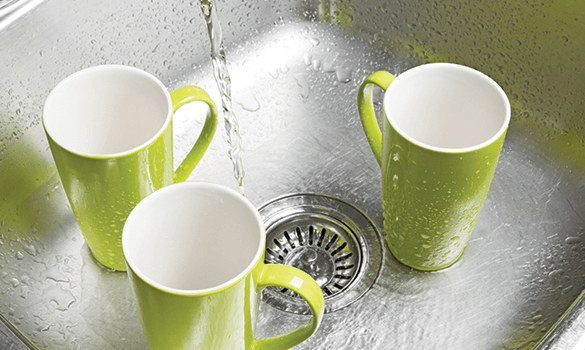 Three green mugs in a kitchen sink with water being poured between them