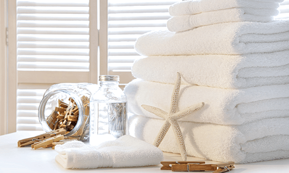 Six white towels stacked on top of each other with another folded towel next to a jar of clothespins
