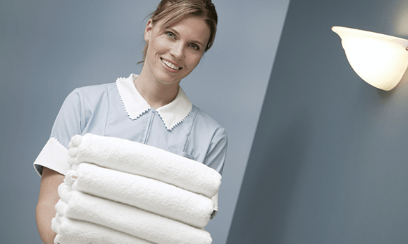 A smiling hotel maid holding four folded white towels