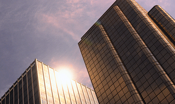 Two tall skyscrapers reflecting sunlight.