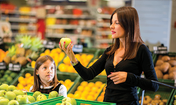 Woman looking at a green apple in a grocery store while her daughter looks on