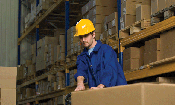 Man in a blue shirt and yellow hard hat pulling a package at a distribution center