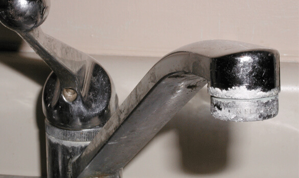 A sink faucet crusted with calcium buildup.