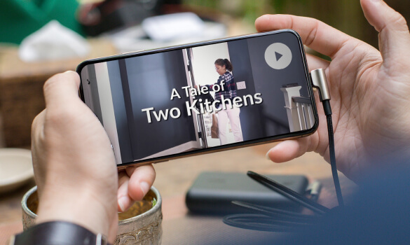 """A person holding a smartphone which has a screen which reads, """"A Tale of Two Kitchens."""""""